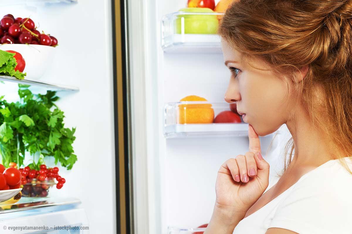 Kind schaut in einen Kühlschrank und fragt sich, was es essen soll