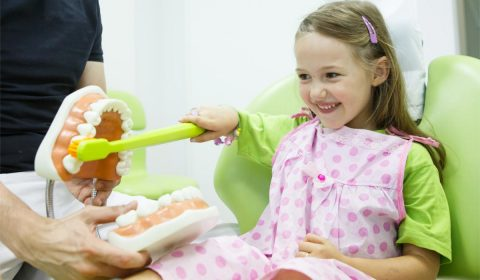 mädchen mit großer zahnbürste in der zahnarztpraxis zahnzoo krefeld